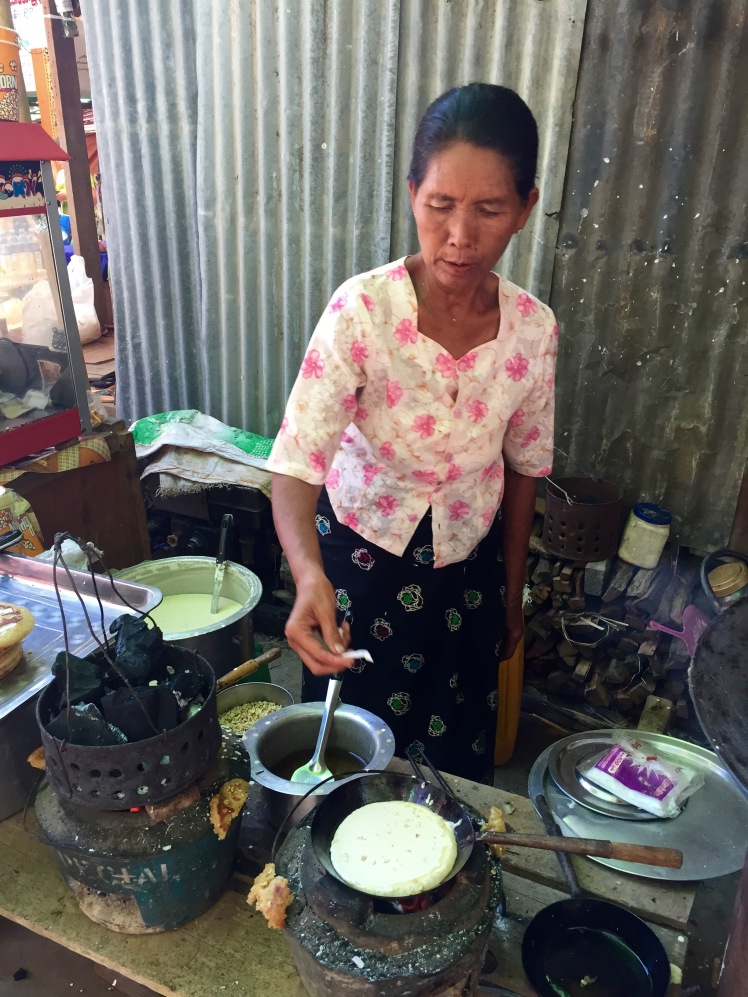 Woman making traditional Burmese pancake, more or less the same as a Western pancake, with peanuts and coconut