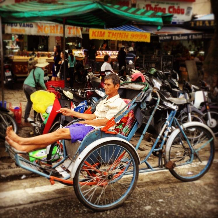 Rickshaw driver parked outside Dong Ba Market, Hue